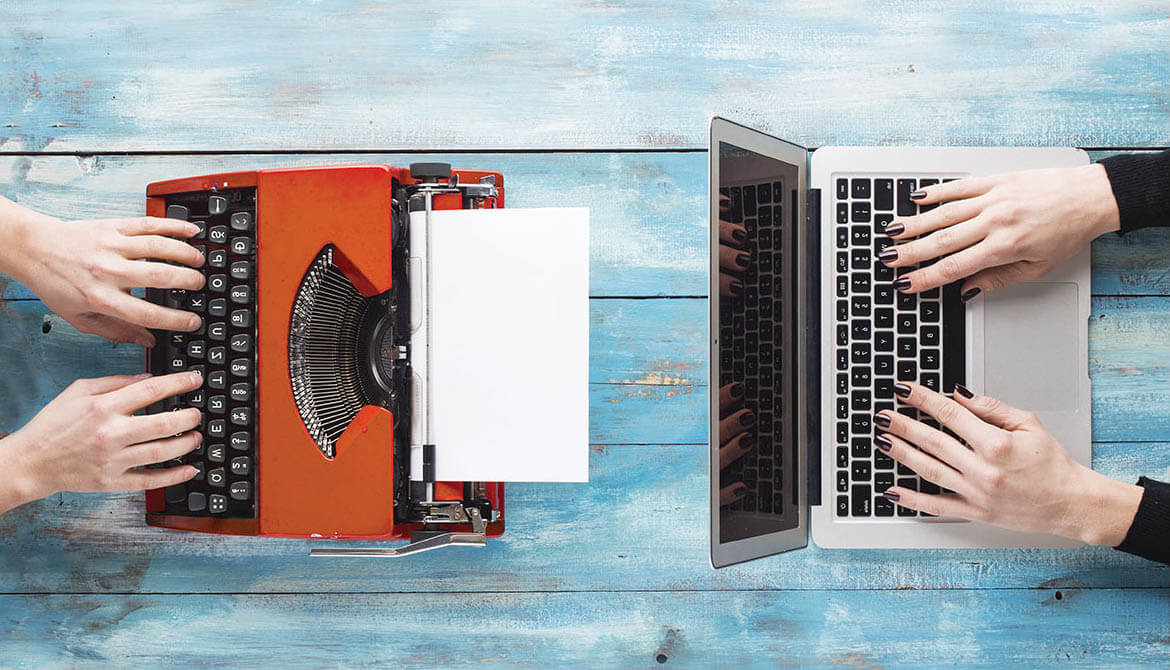 an old red typewriter across from a sleek new Mac laptop