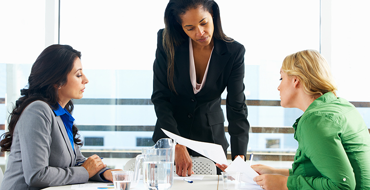 women sitting around desk going over papers