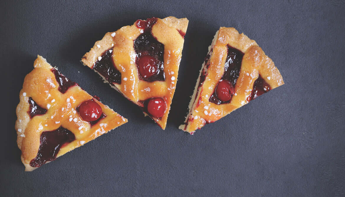 three pieces of cherry pie on a gray backdrop, one slightly smaller than the other two
