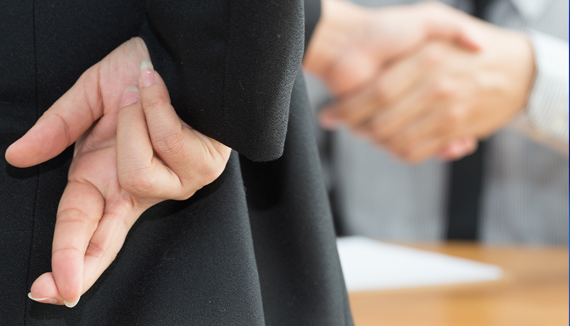 Businessman showing fingers crossed behind his back while he shakes hands