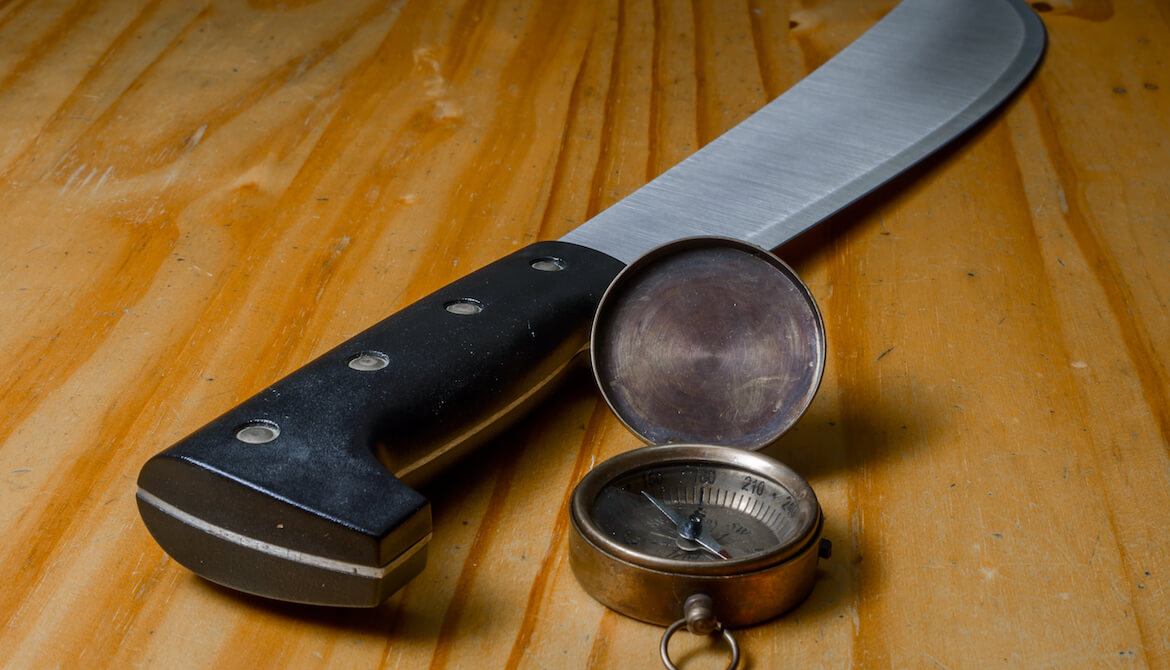 Machete and compass in wood background