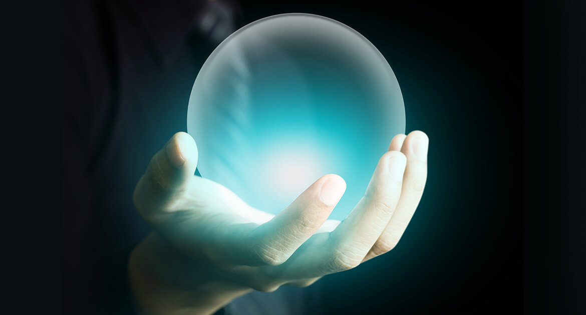 Hand of a business man holding a crystal ball glowing aqua blue