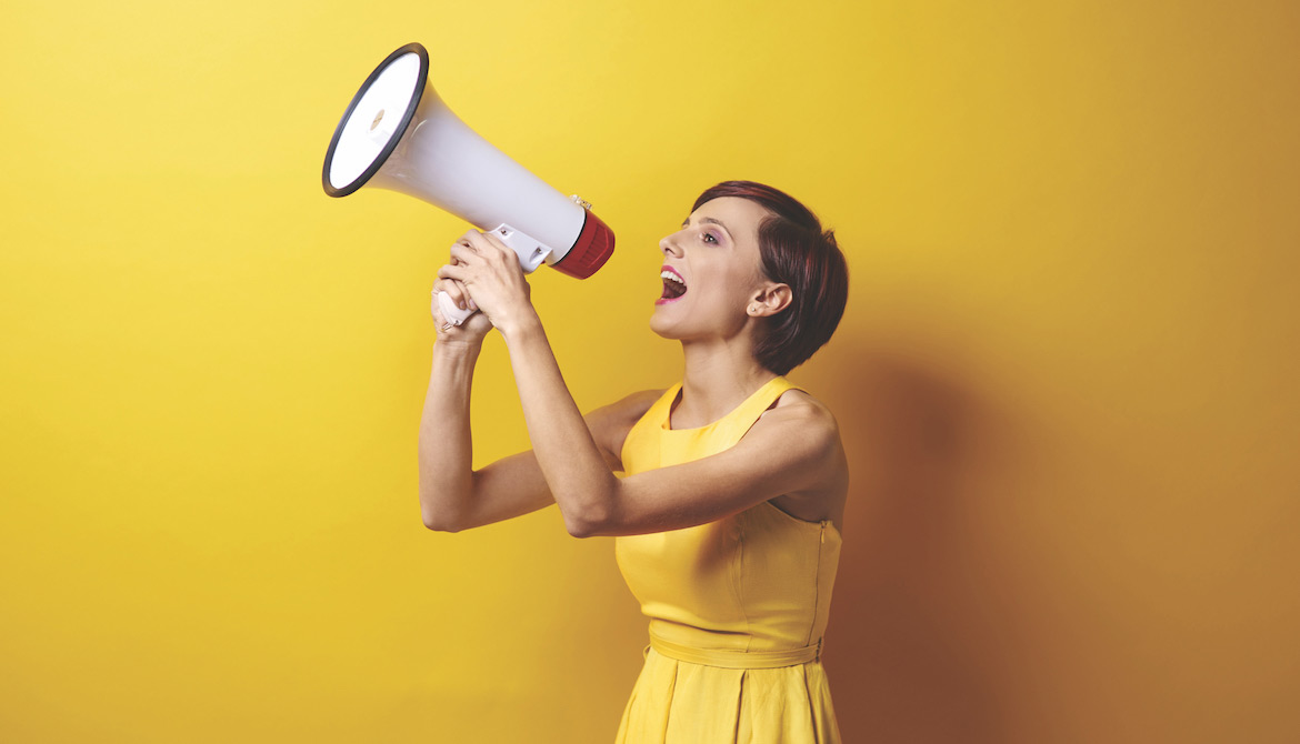 woman in a yellow dress using a bullhorn or megaphone