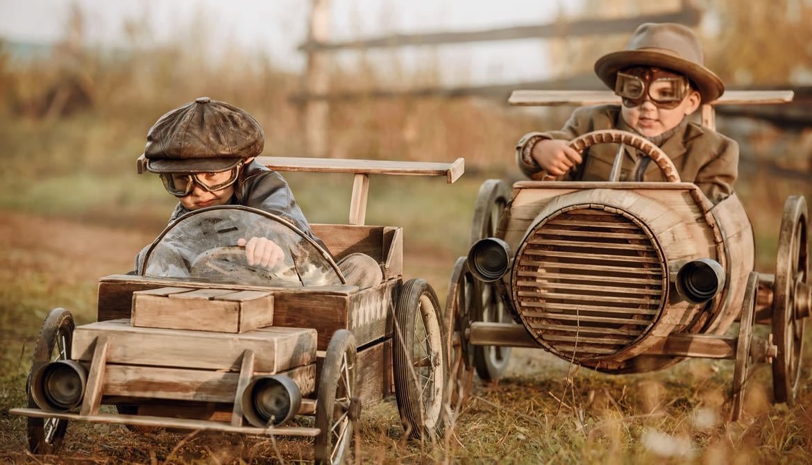 Two boys in helmets and goggles racing in wooden toy cars