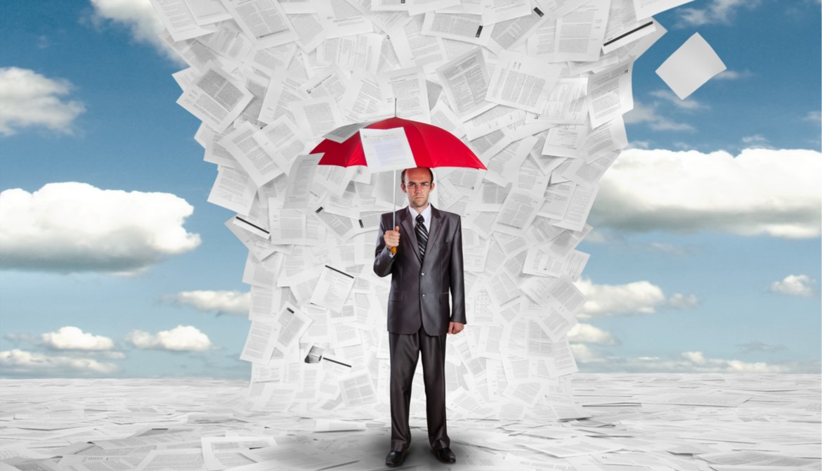 businessman holding umbrella under a deluge of documents
