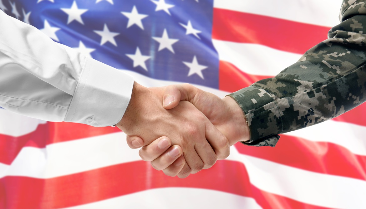 civilian and military arms shake hands in front of a U.S. flag