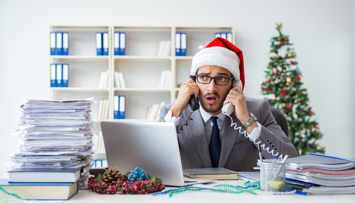 Stressed businessman celebrating Christmas in the office