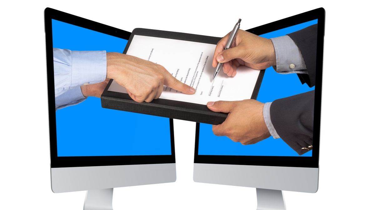hands coming out of computers taking an e-signature on a contract