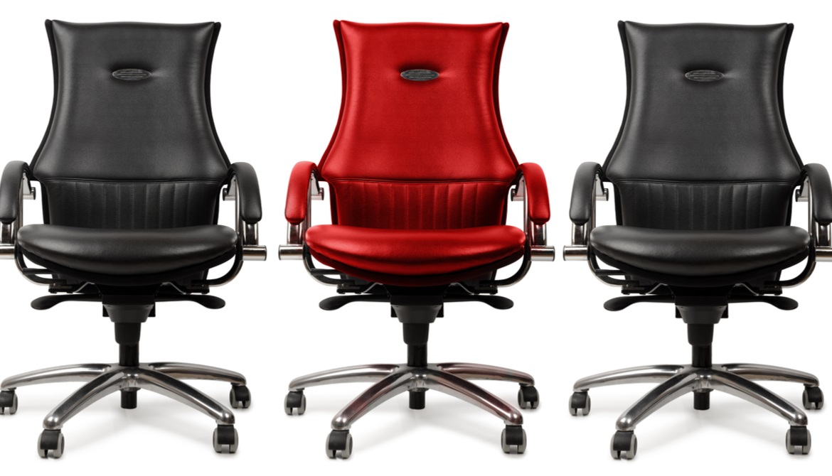 black executive chairs on either side of a red executive chair