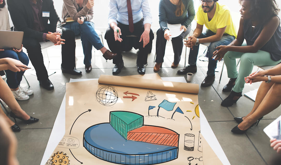 group of professional workers sitting in a circle looking at a colorful graph on the floor