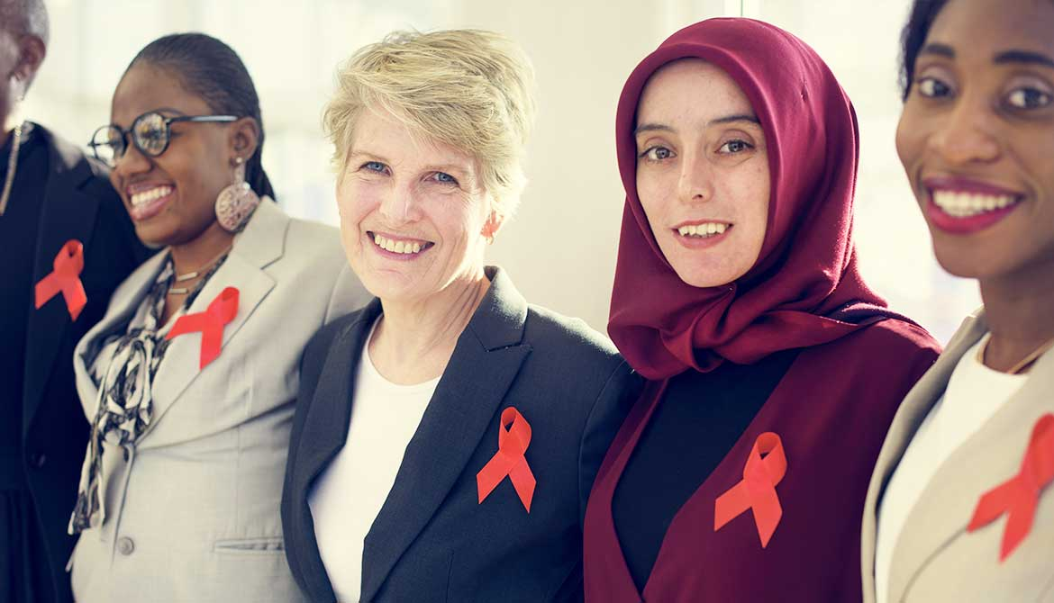 diverse group of women standing shoulder to shoulder wearing orange partnership ribbons