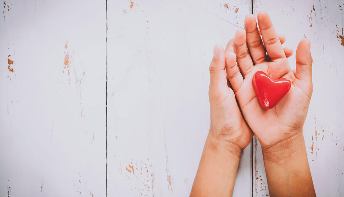 hands holding a red heart over a white wooden background