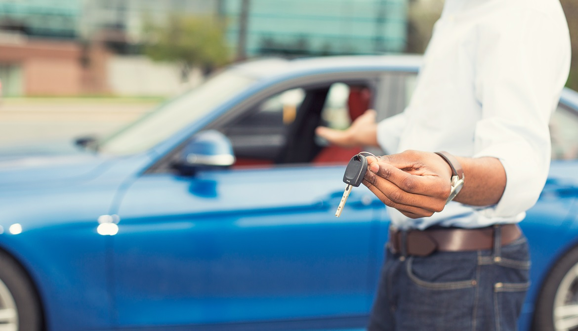 African American man holding out keys to a new blue car