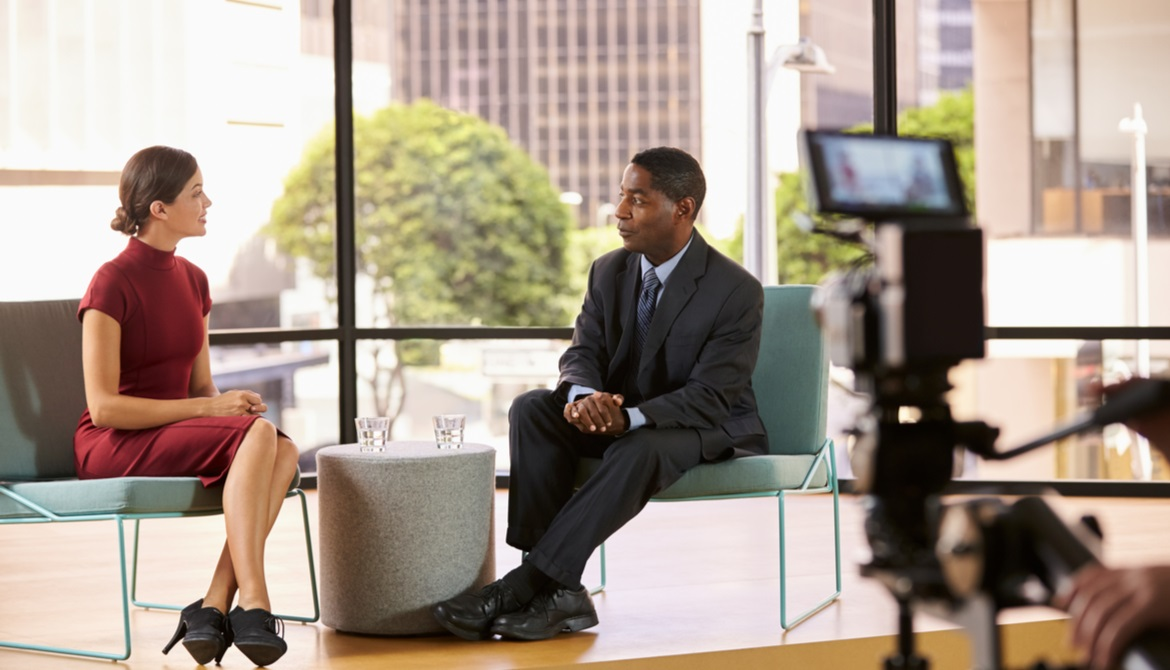 female TV anchor interviewing an African American businessman on camera