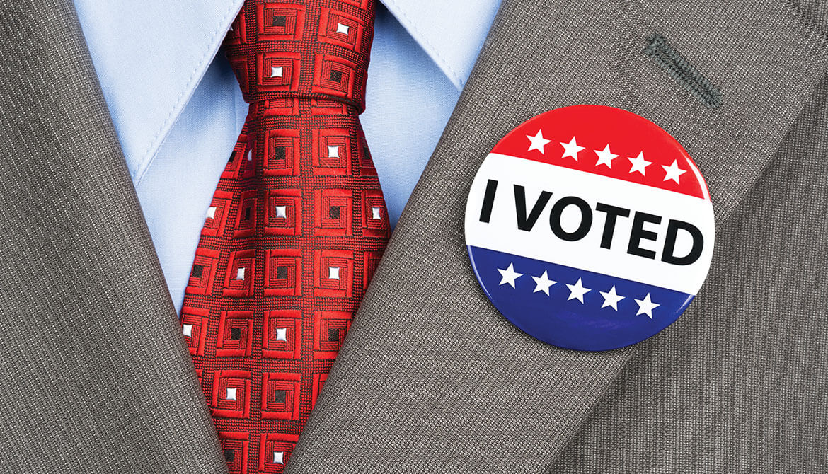 red tie and suit lapel with I Voted button