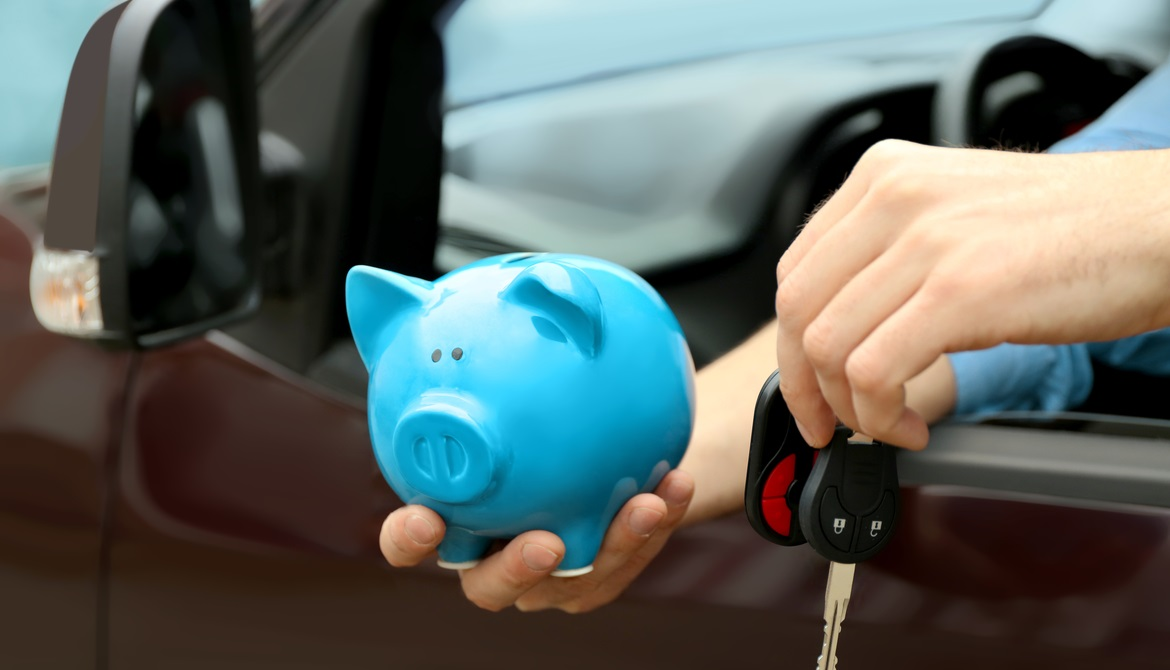 man holding blue piggy bank and car keys out car window