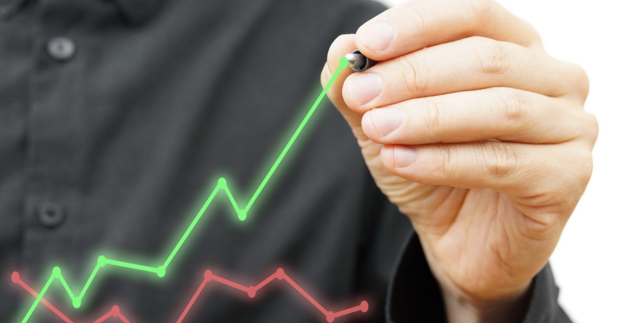 Man in black shirt drawing a green financial graph above an existing red financial graph