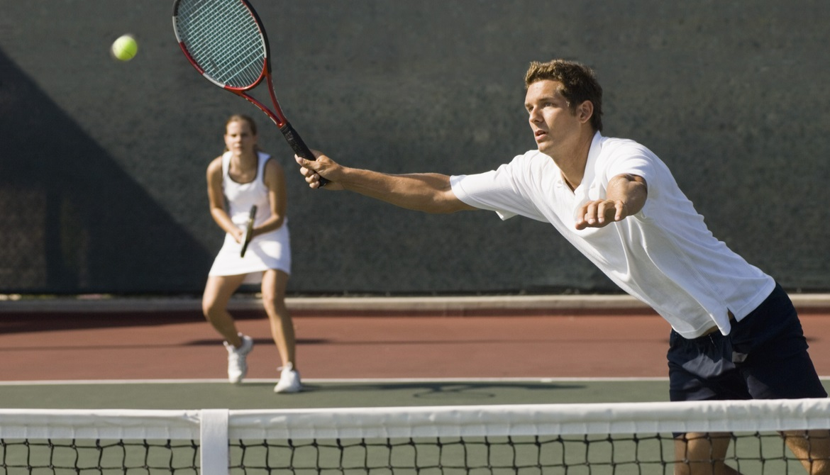 a man and a woman playing doubles tennis