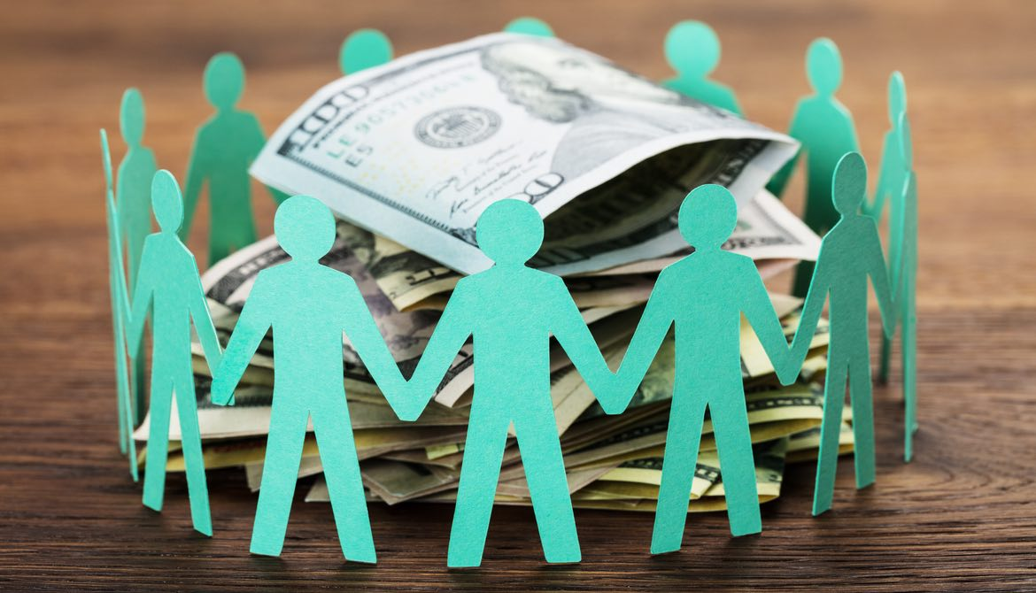 green paper cutout people encircling some money