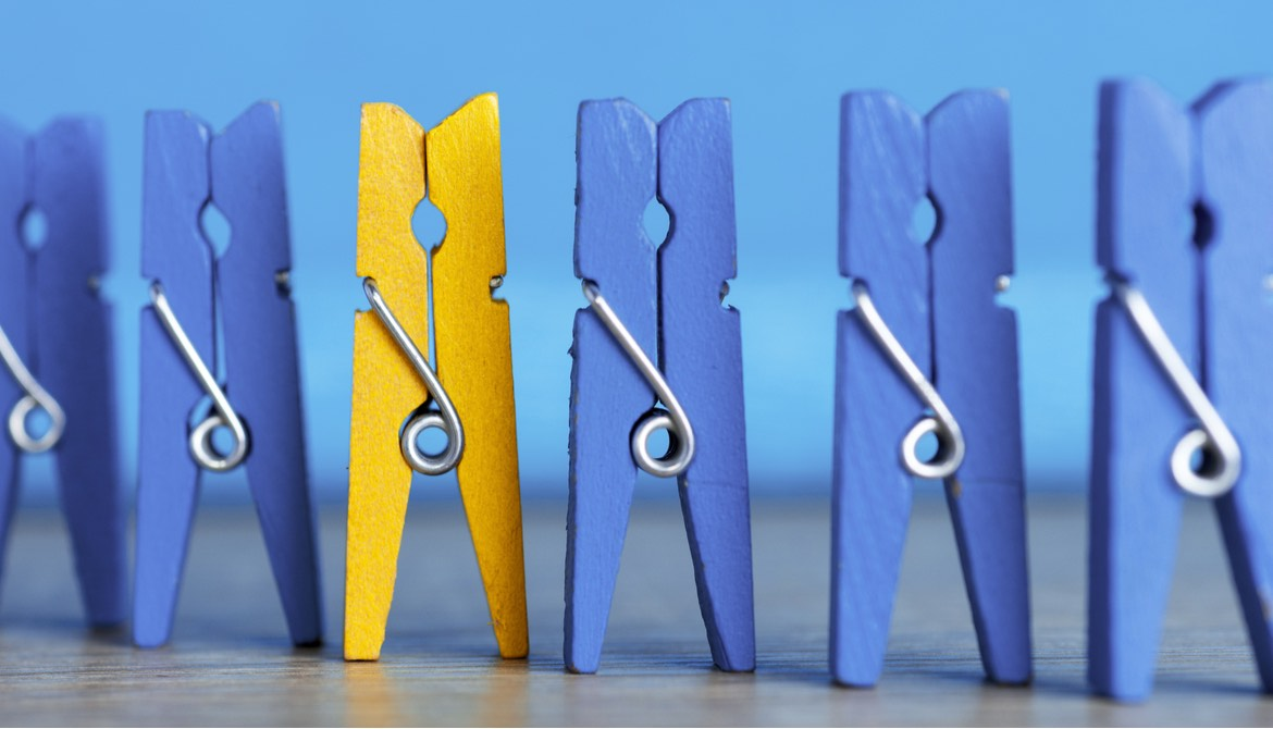 line up of blue clothespins with one yellow one