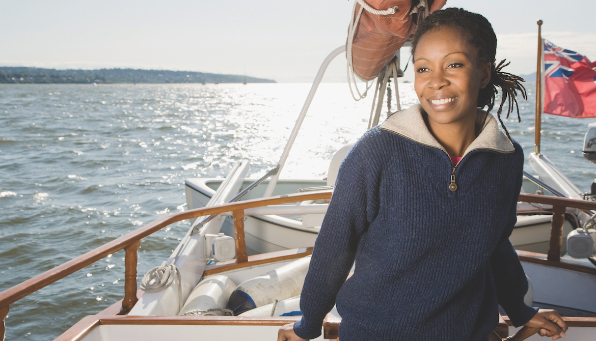 smiling African American woman sailing a sailboat