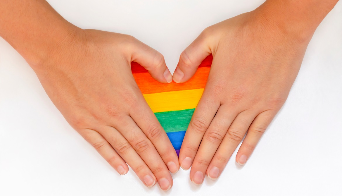 hands forming a heart over a rainbow