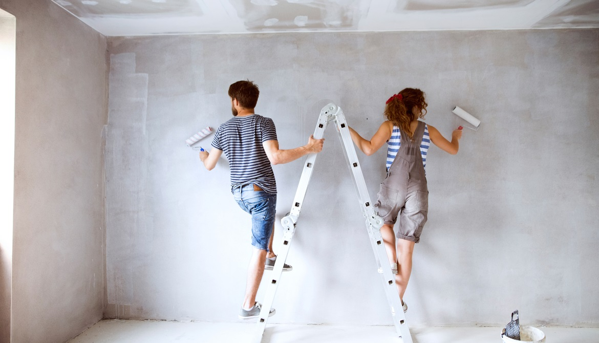young couple on a ladder painting walls of new house