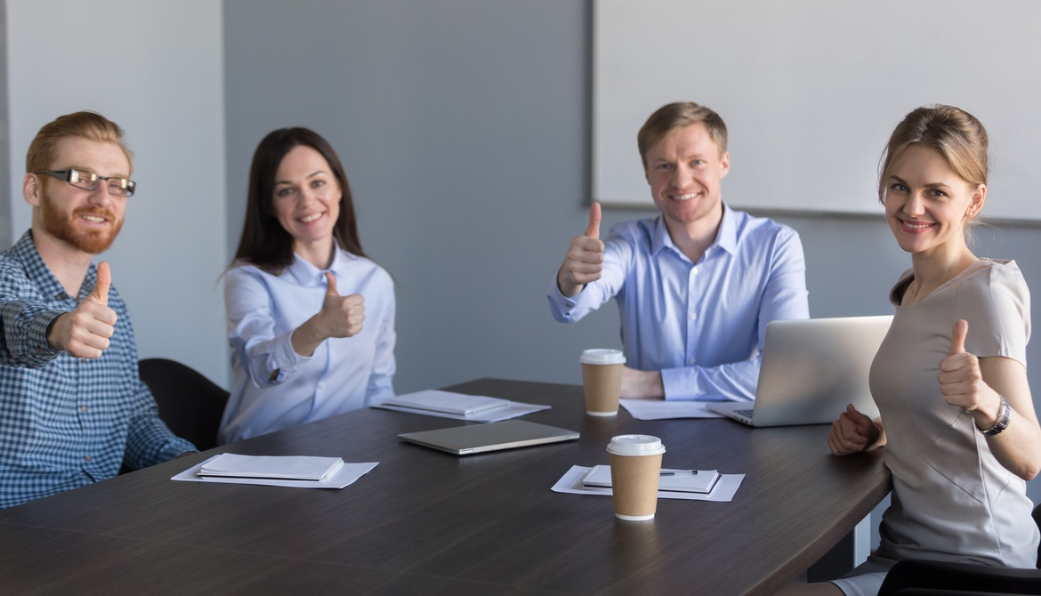 young executives around a table giving thumbs up