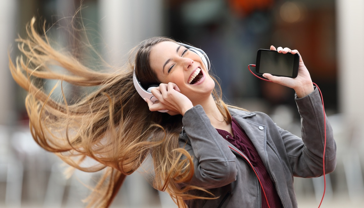 young woman dancing with cell phone and hair flying