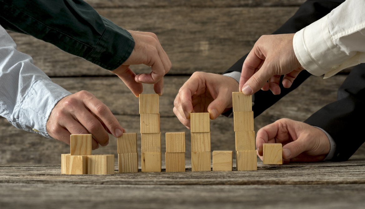 executives stacking wooden blocks