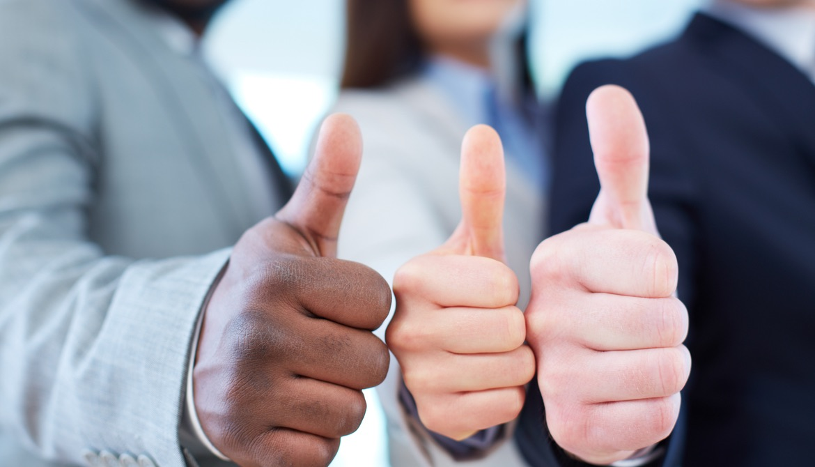 three executives of diverse ethnicities with their thumbs up