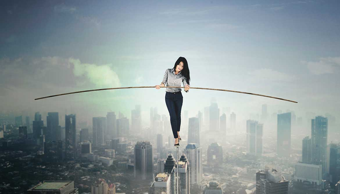 businesswoman holding a stick to balance while walking on a tightrope above a city