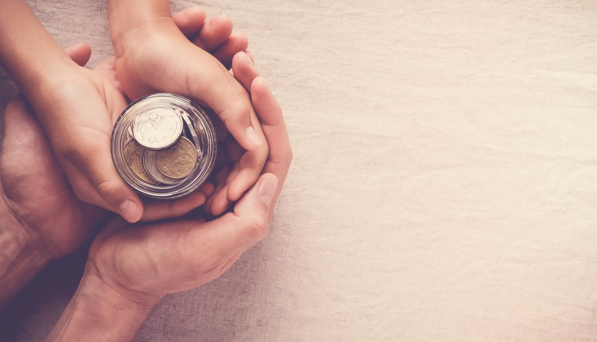 adult hands holding child's hands around a savings jar