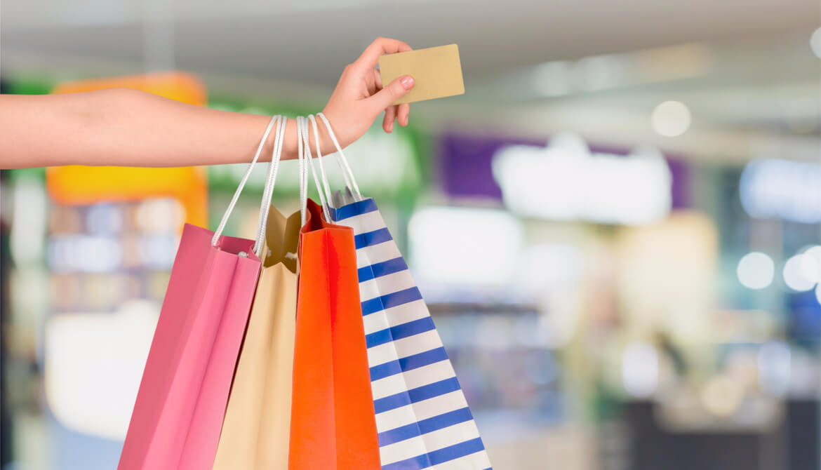 woman with several colorful shopping bags holding credit card