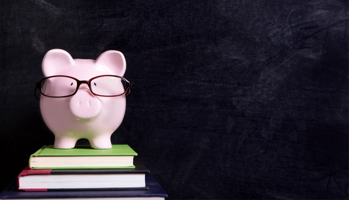 piggybank wearing glasses standing on a stack of books