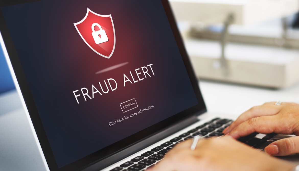 hands typing on laptop with screen displaying fraud alert