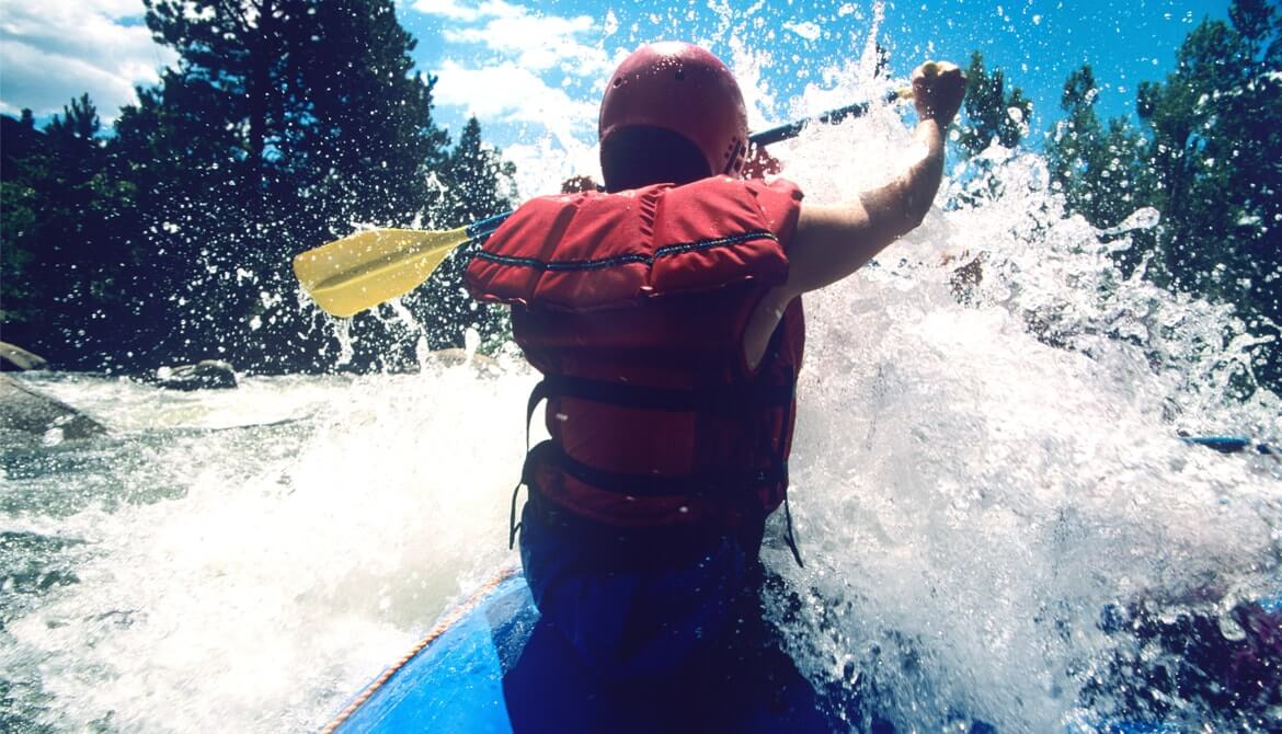 male kayaker paddling through rapids