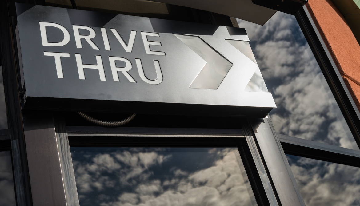 metal drive thru sign on a windowed exterior wall displaying reflection of clouds in the sky