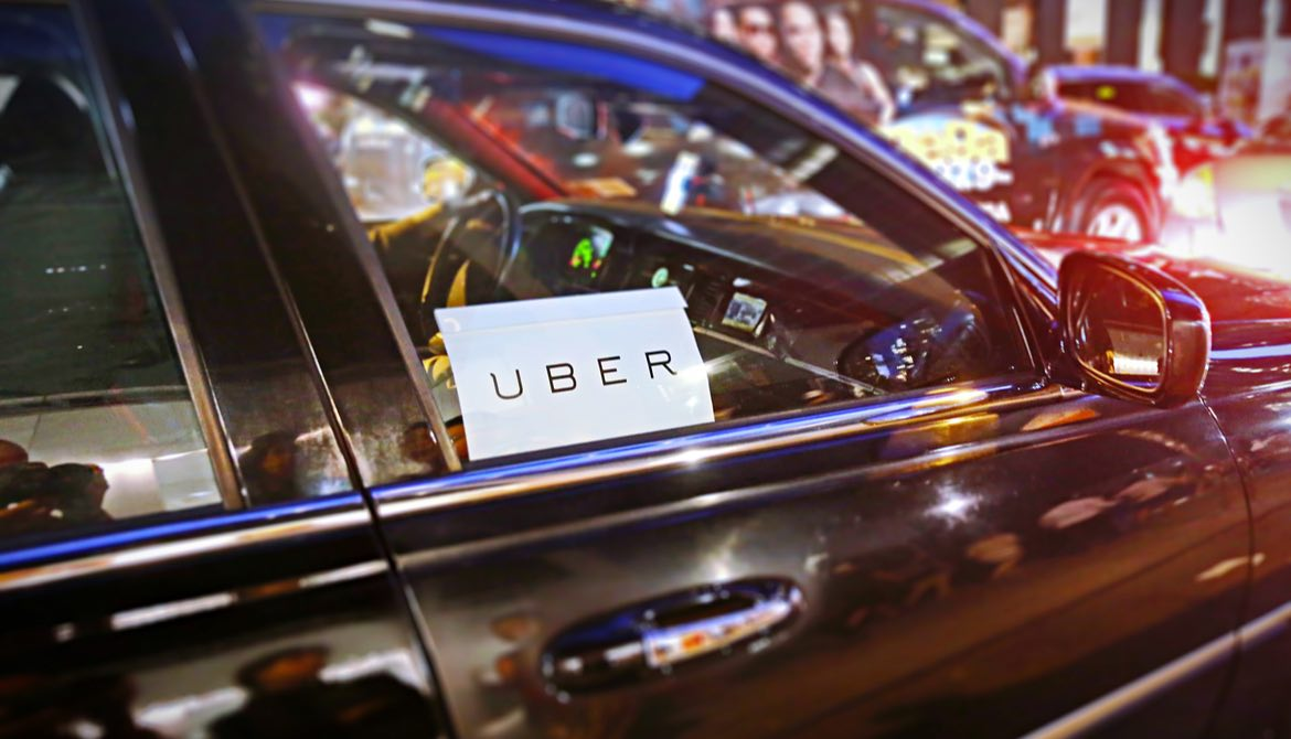 car with uber sign in window
