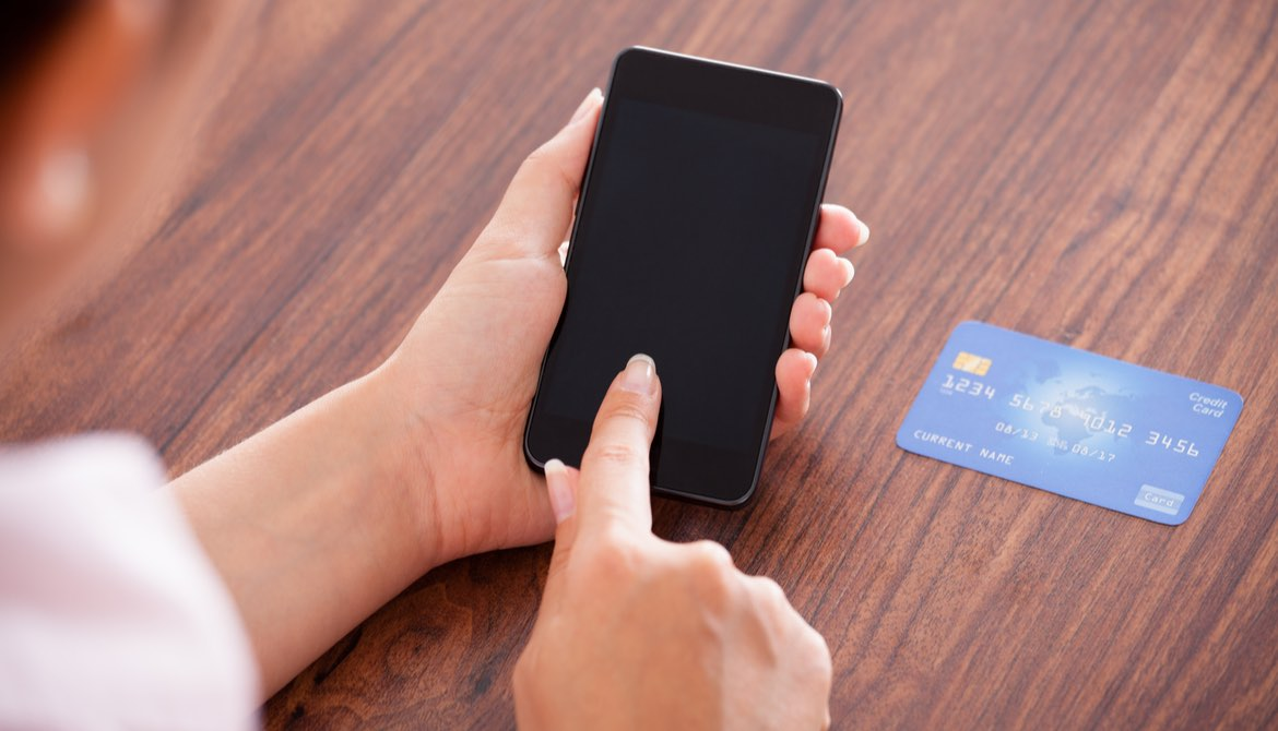 woman using smartphone with credit card to make a payment