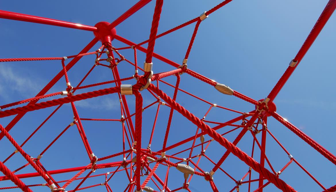 red jungle gym on blue sky