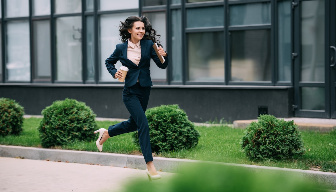 young happy businesswoman running to work in high heels with coffee and notebook