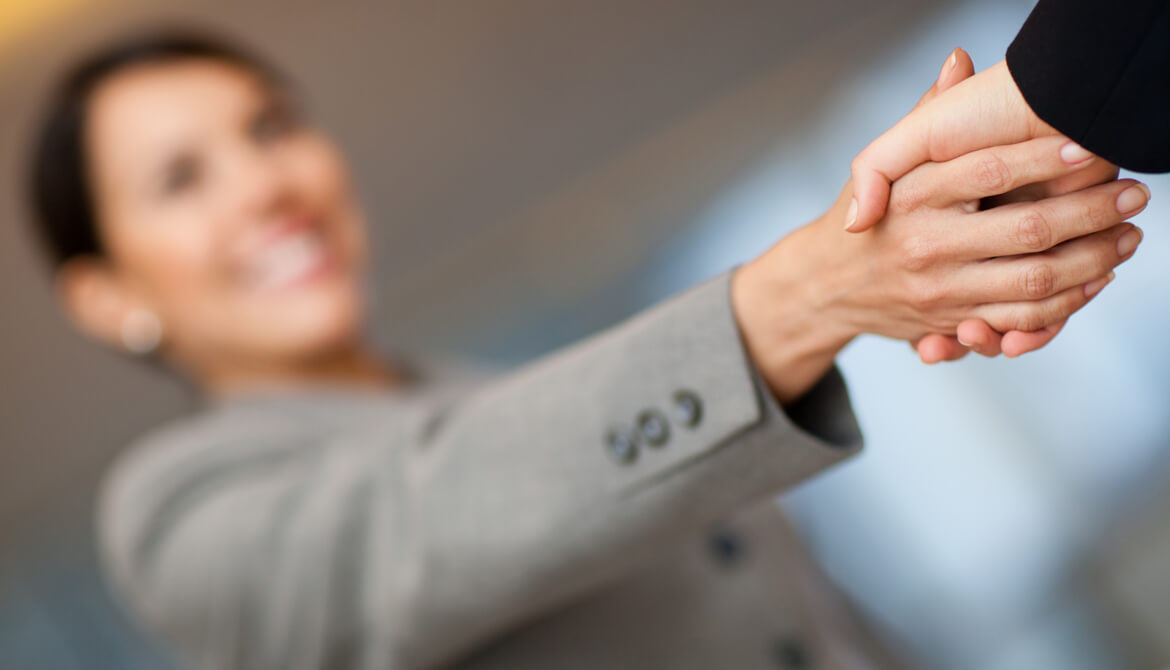 smiling businesswoman greeting a member with a handshake