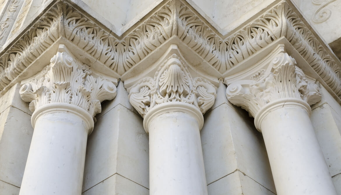 three classical Roman composite columns holding up an ornate frieze