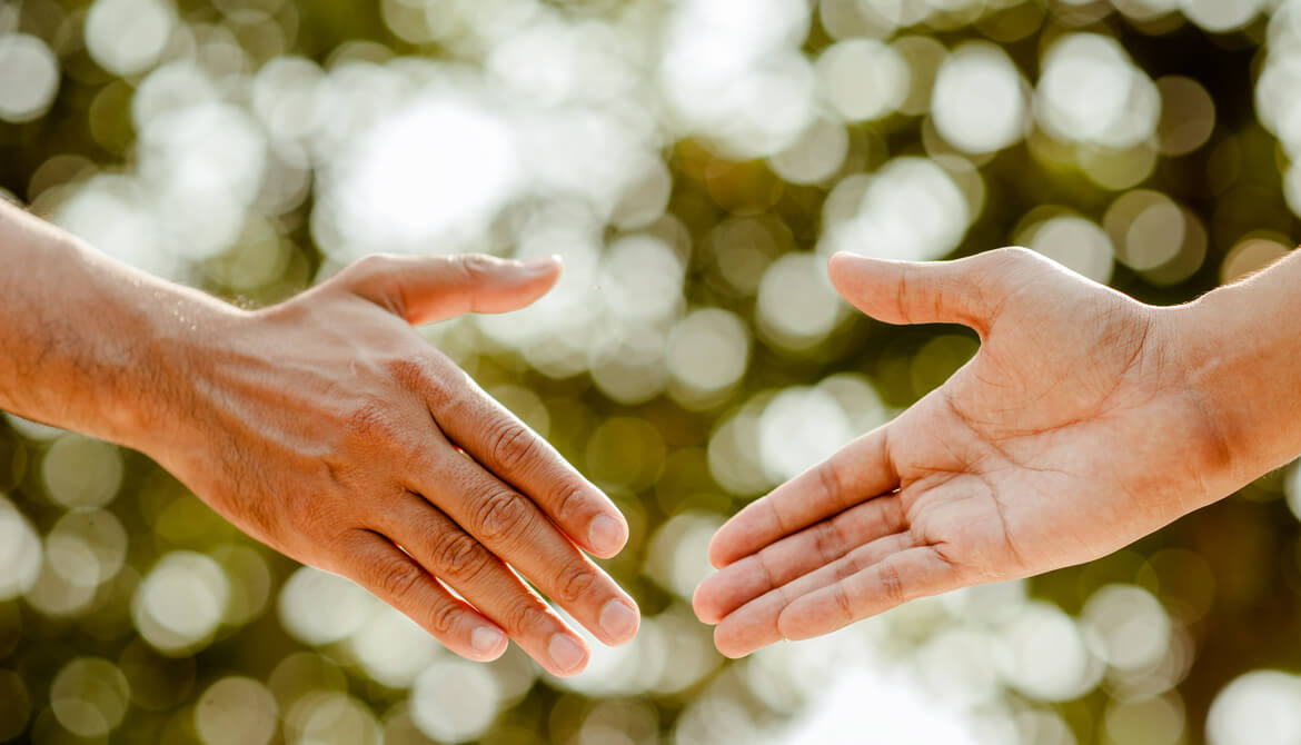 hand held out in gesture of trust and assistance while another hand reaches out to take it