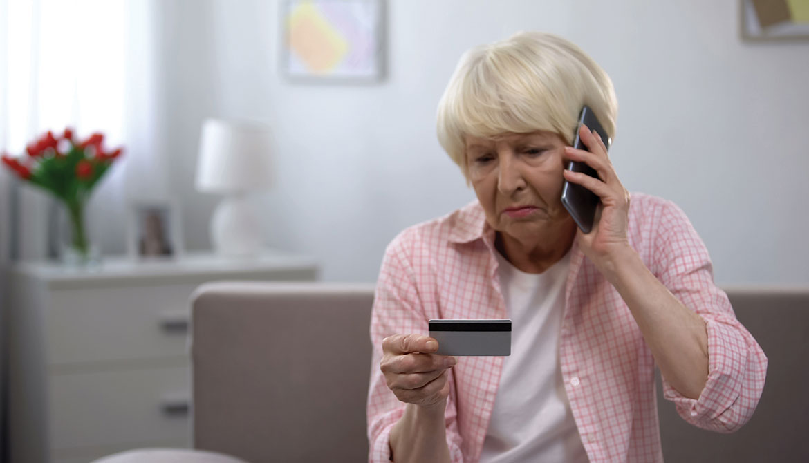 upset elderly woman on phone looking at credit card