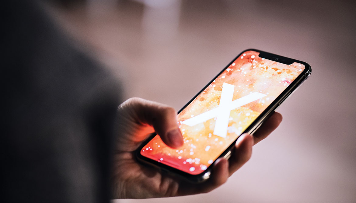 person holding smartphone with glowing X on screen