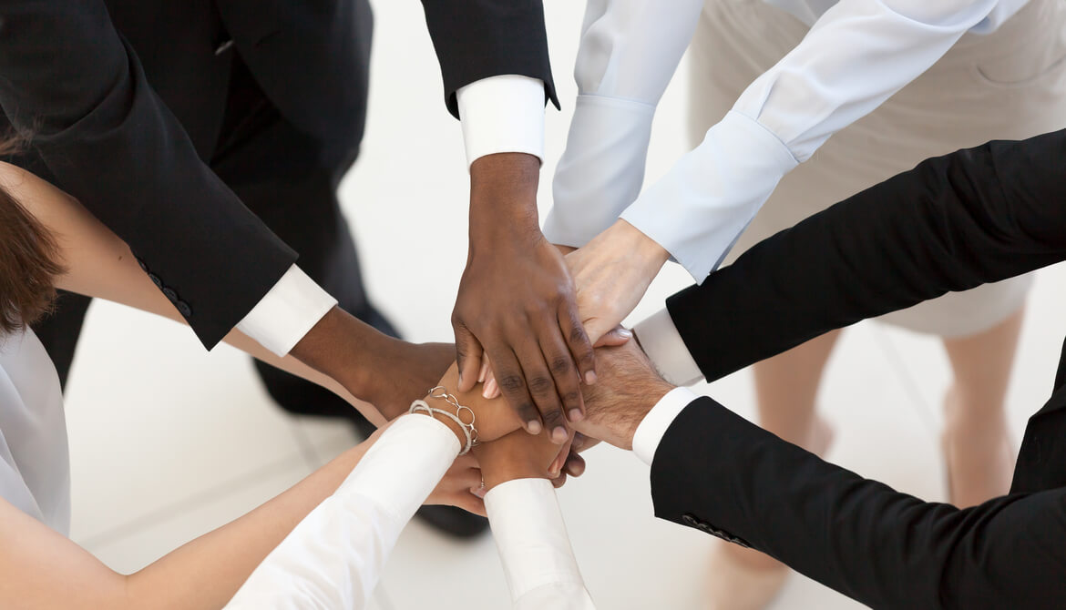 diverse business people put hands together