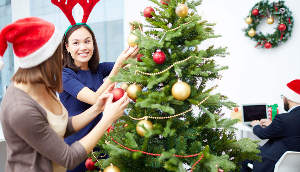 festive businesswomen decorating office for holidays while colleague works on a laptop