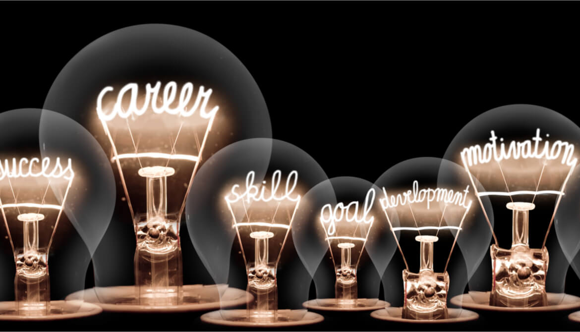 lightbulbs with glowing filaments in the shape of career and development related words